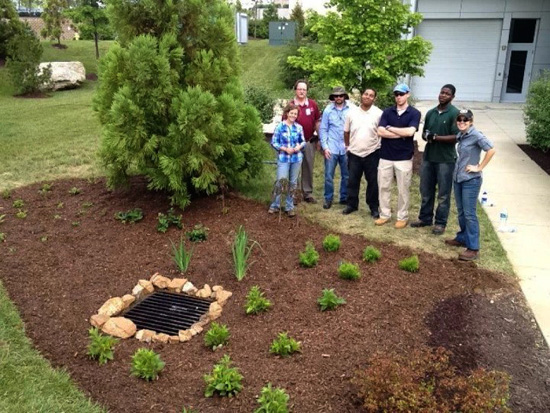 READY program participants pose next to a finished rain garden