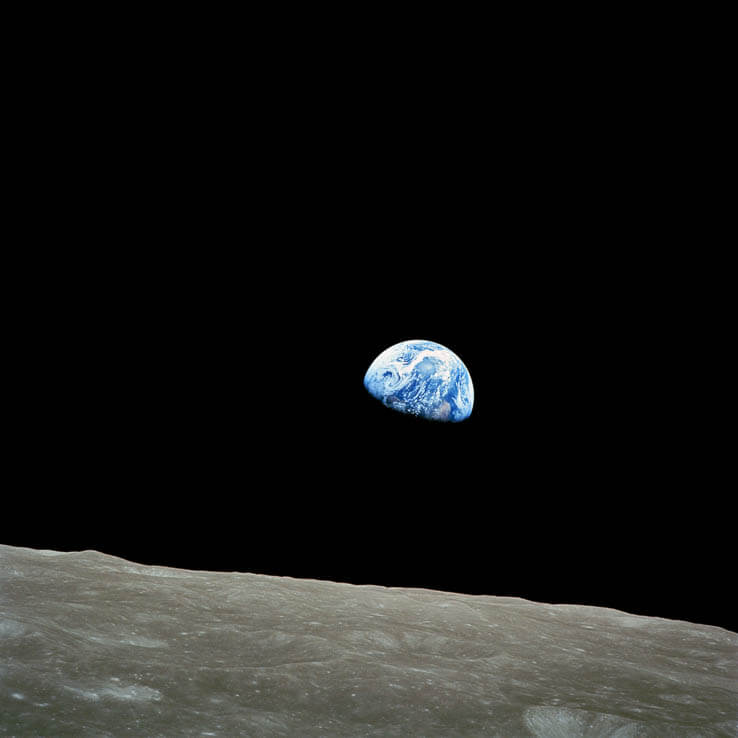 Planet Earth is seen with the edge of the moon in the foreground