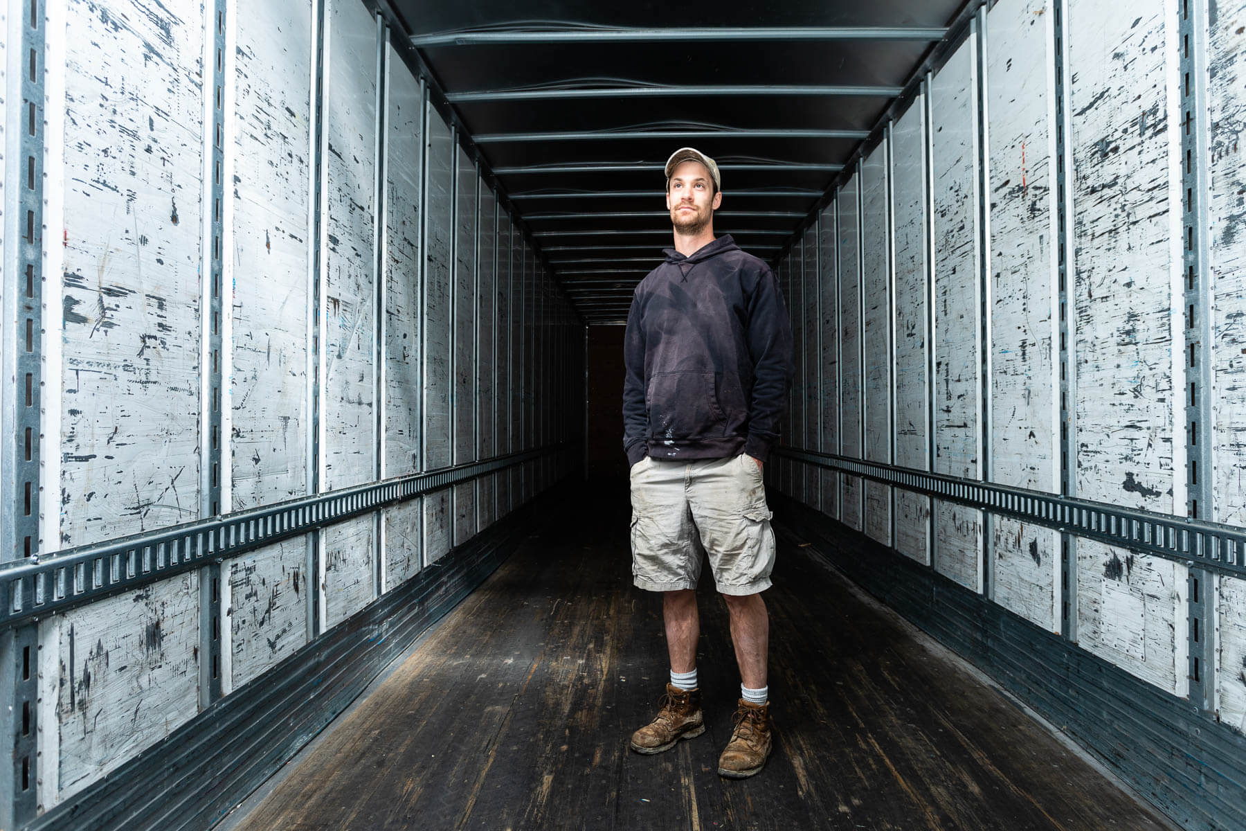 Man stand inside empty metal rectangular container of semi-truck
