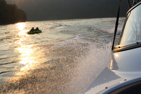 Two people in a tube get pulled by a boat on Raystown Lake.