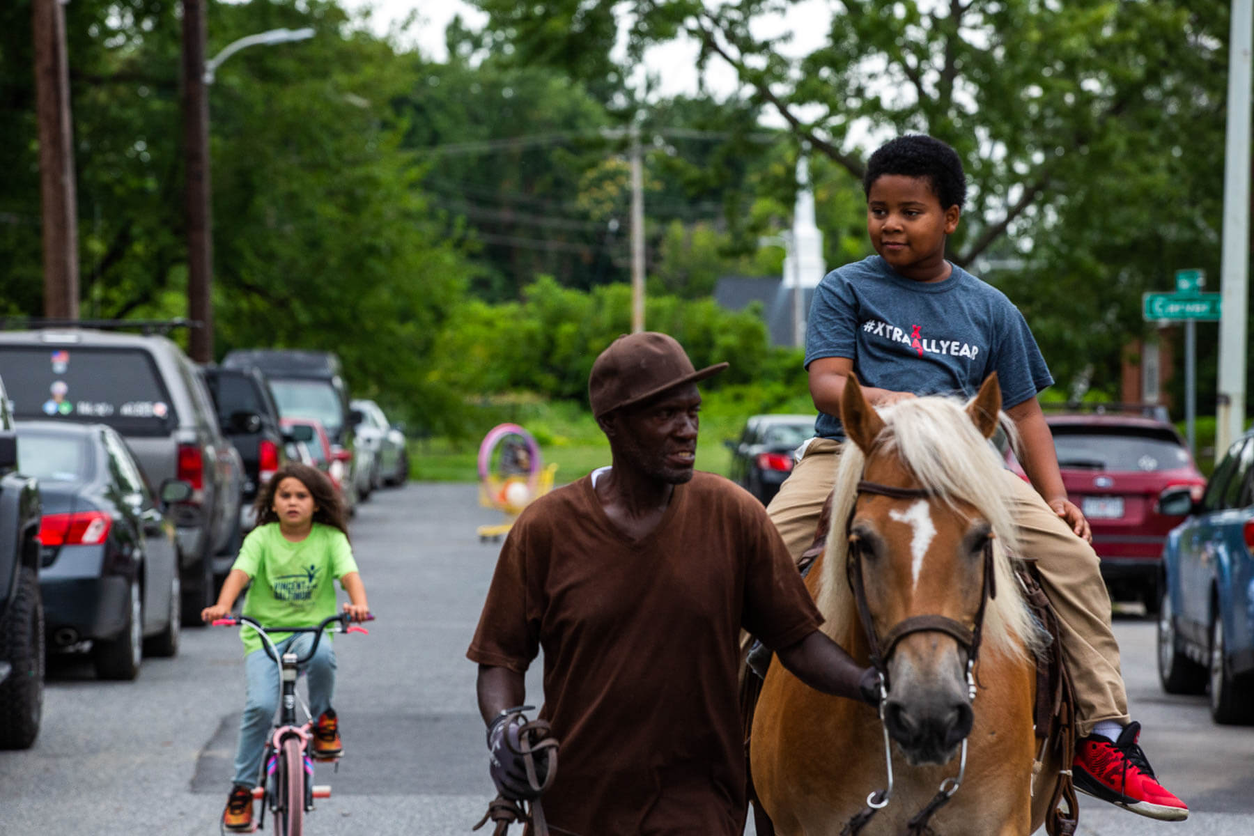 A young boy rides a horse down the street in Turner Station.