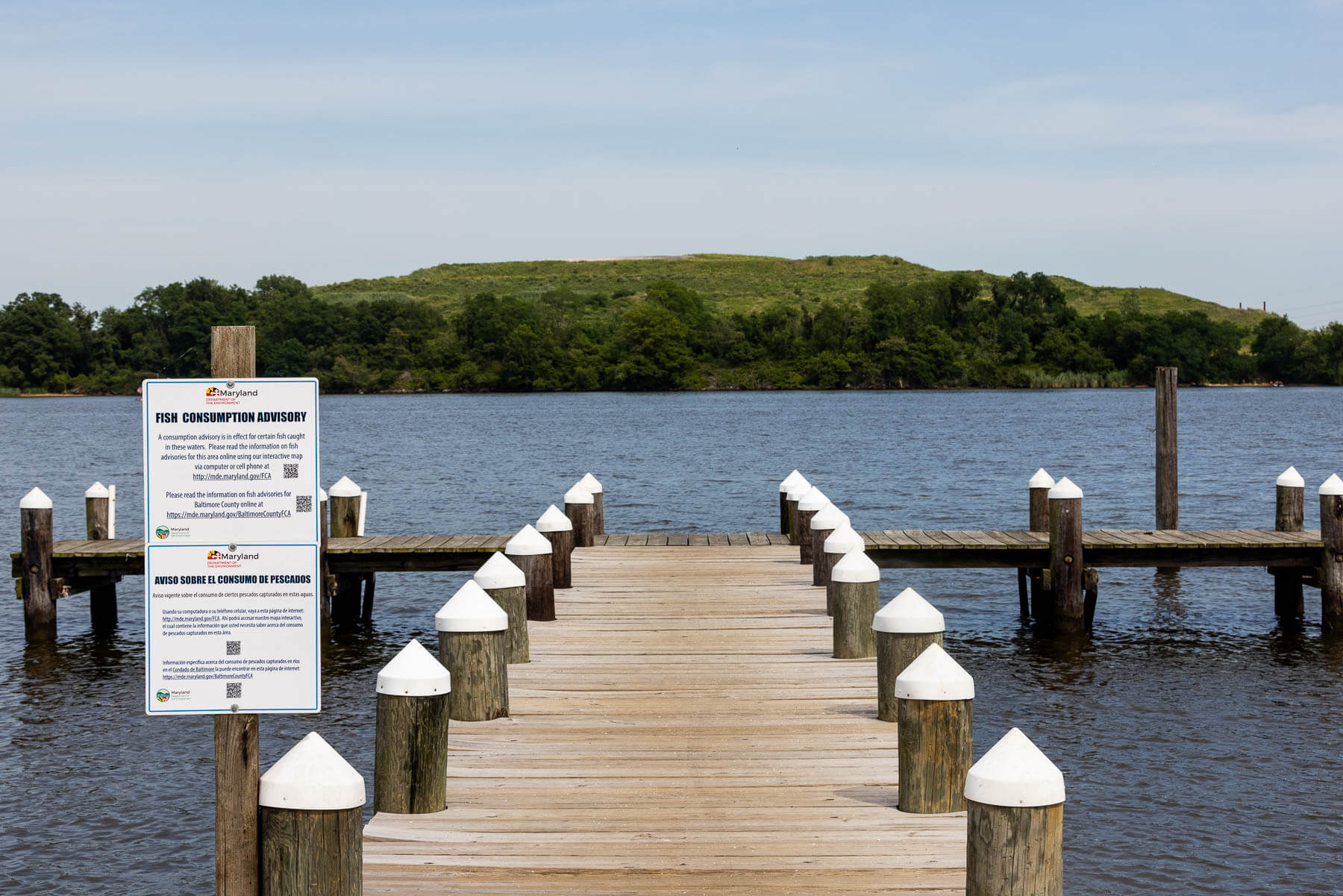 An empty pier with a fish consumption advisory sign.
