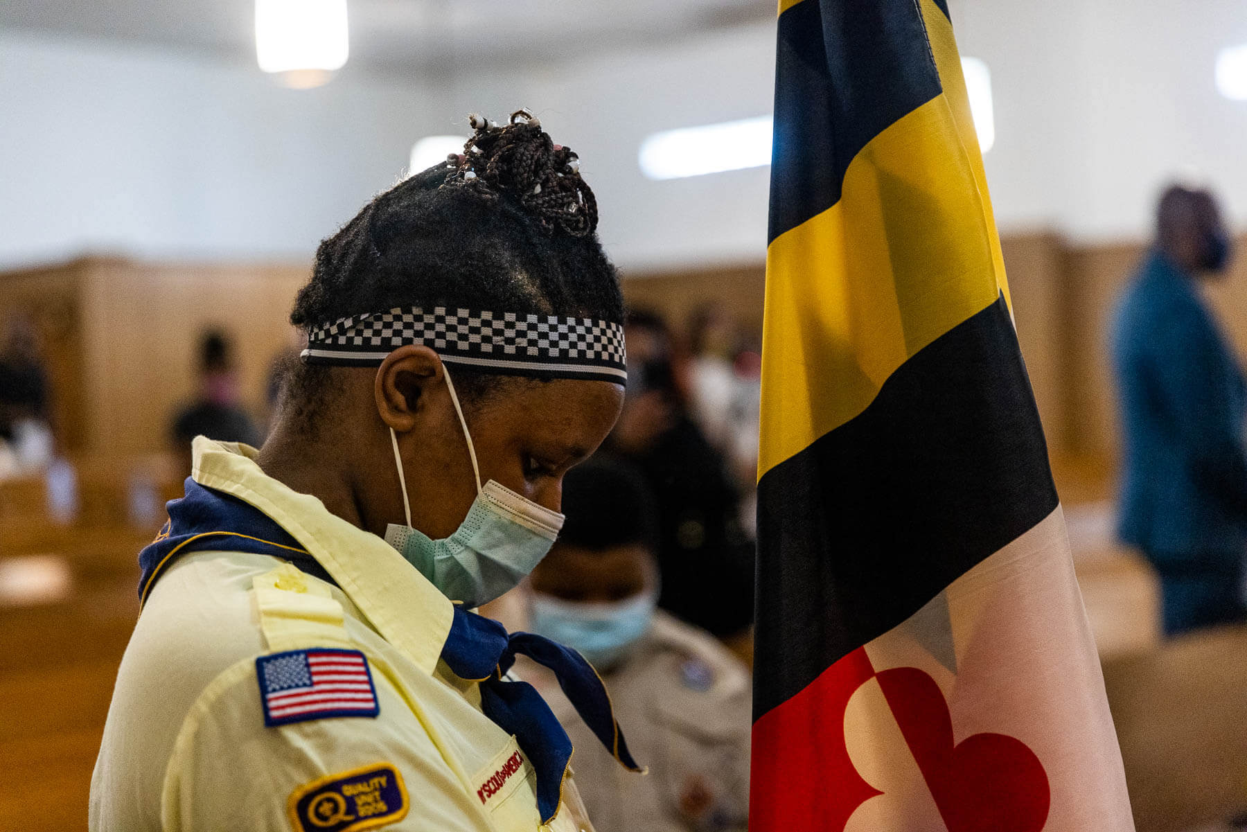 A boy scout member prepares the Maryland flag.