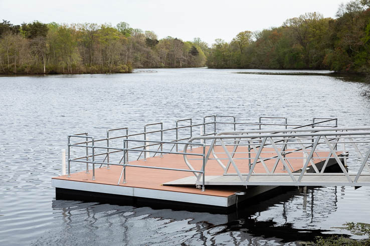 A ramp leads to a platform floating on a calm man-made lake