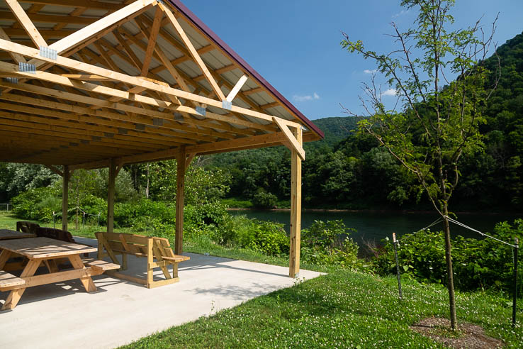 A wooden pavilion overlooks a wide river and forested hills on the opposite bank
