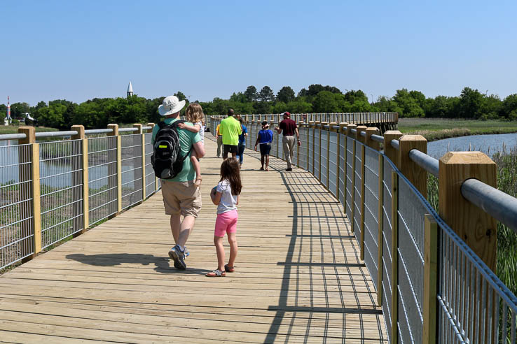 A man and two children walk on a wooden boardwalk over a winding creek.