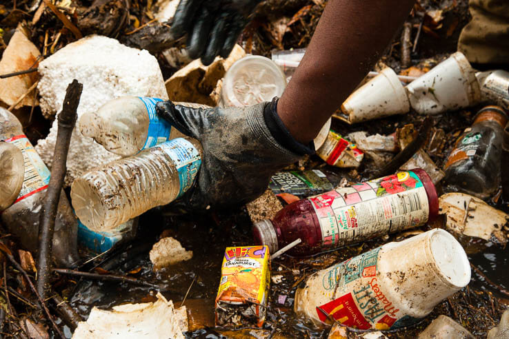 Gloved hand picks up dirty plastic bottles in water choked with plastic trash
