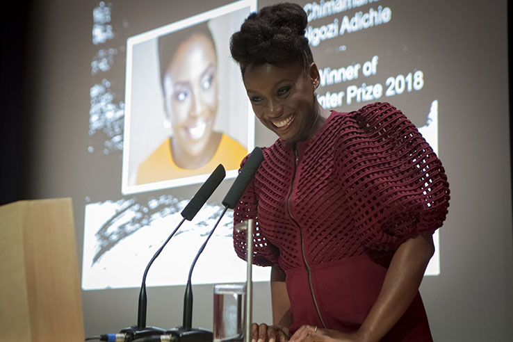 African woman smiles while standing behind podium