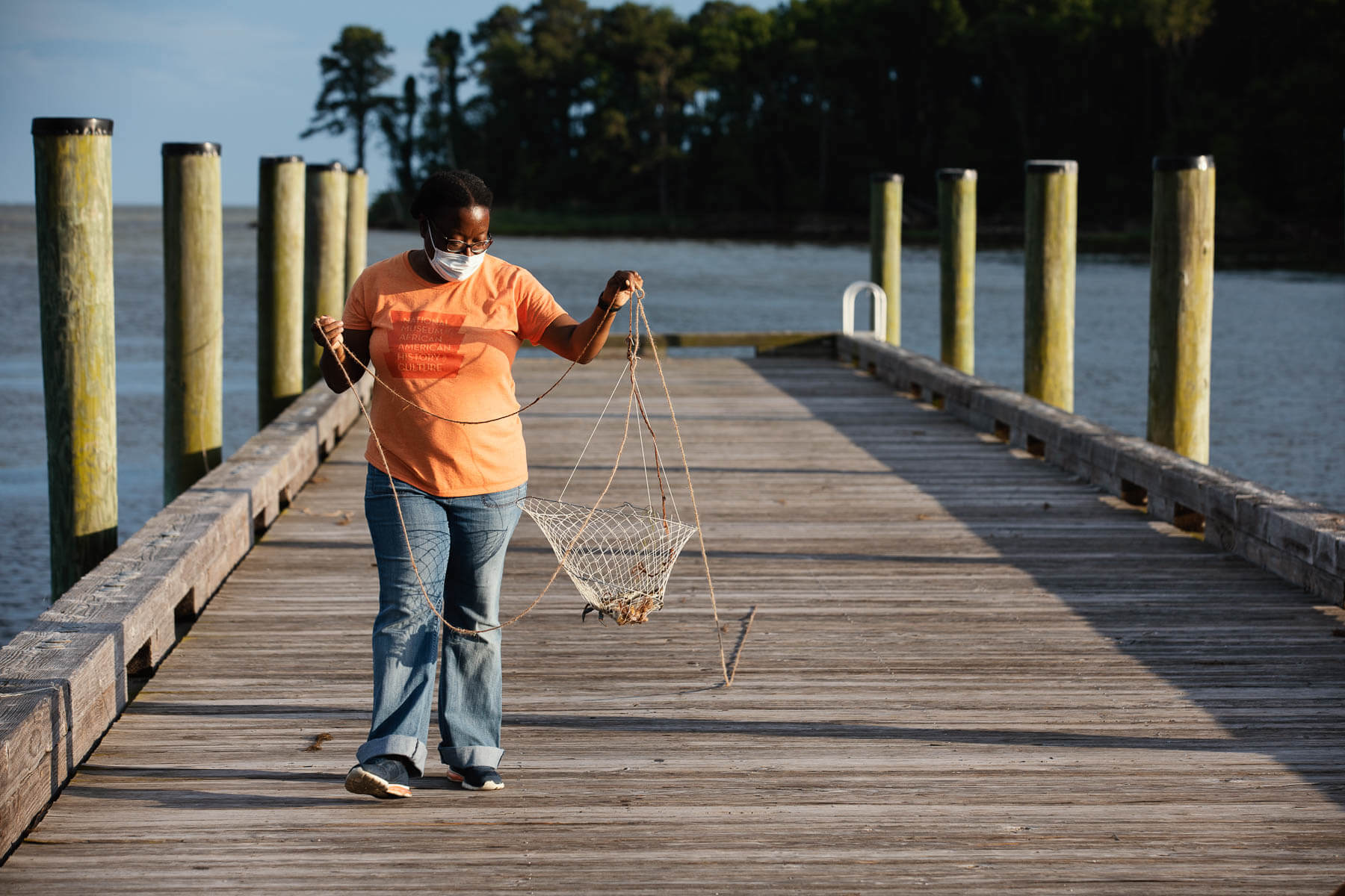 Woman carries a crab in a net