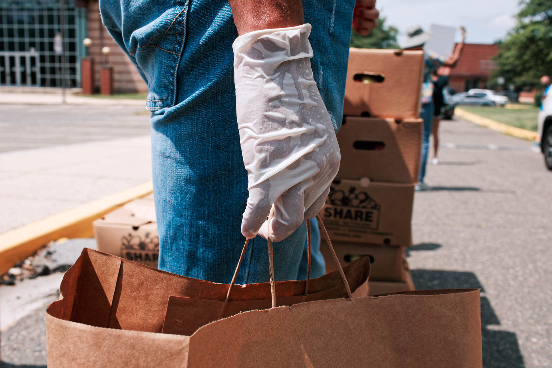 Hand holds paper bag of donations