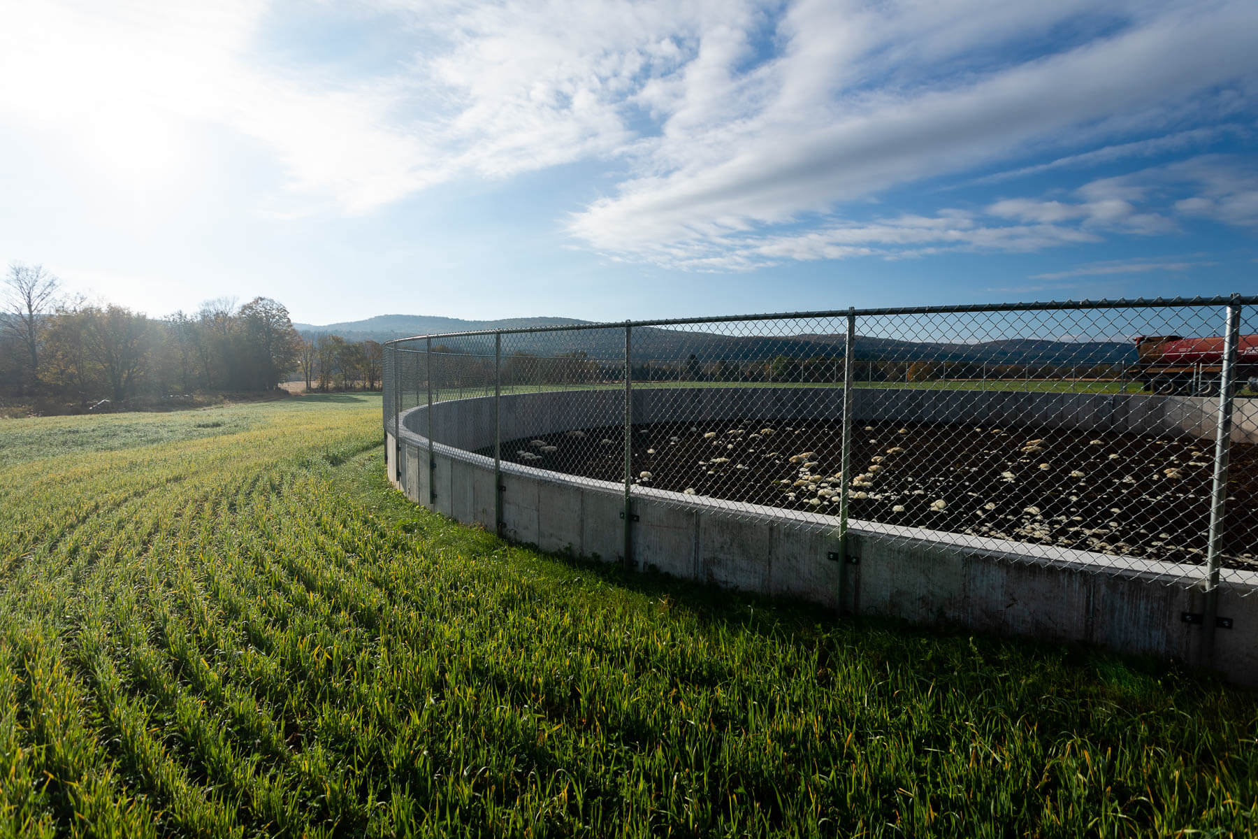 A large round manure pit next to expansive crops