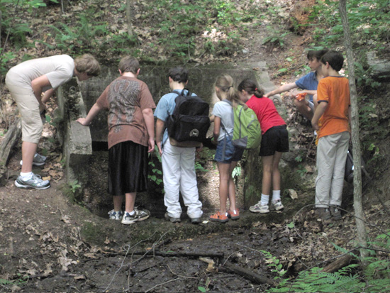 A group of environmental education program participants peak into a culvert at Bull Run Mountains Conservancy.