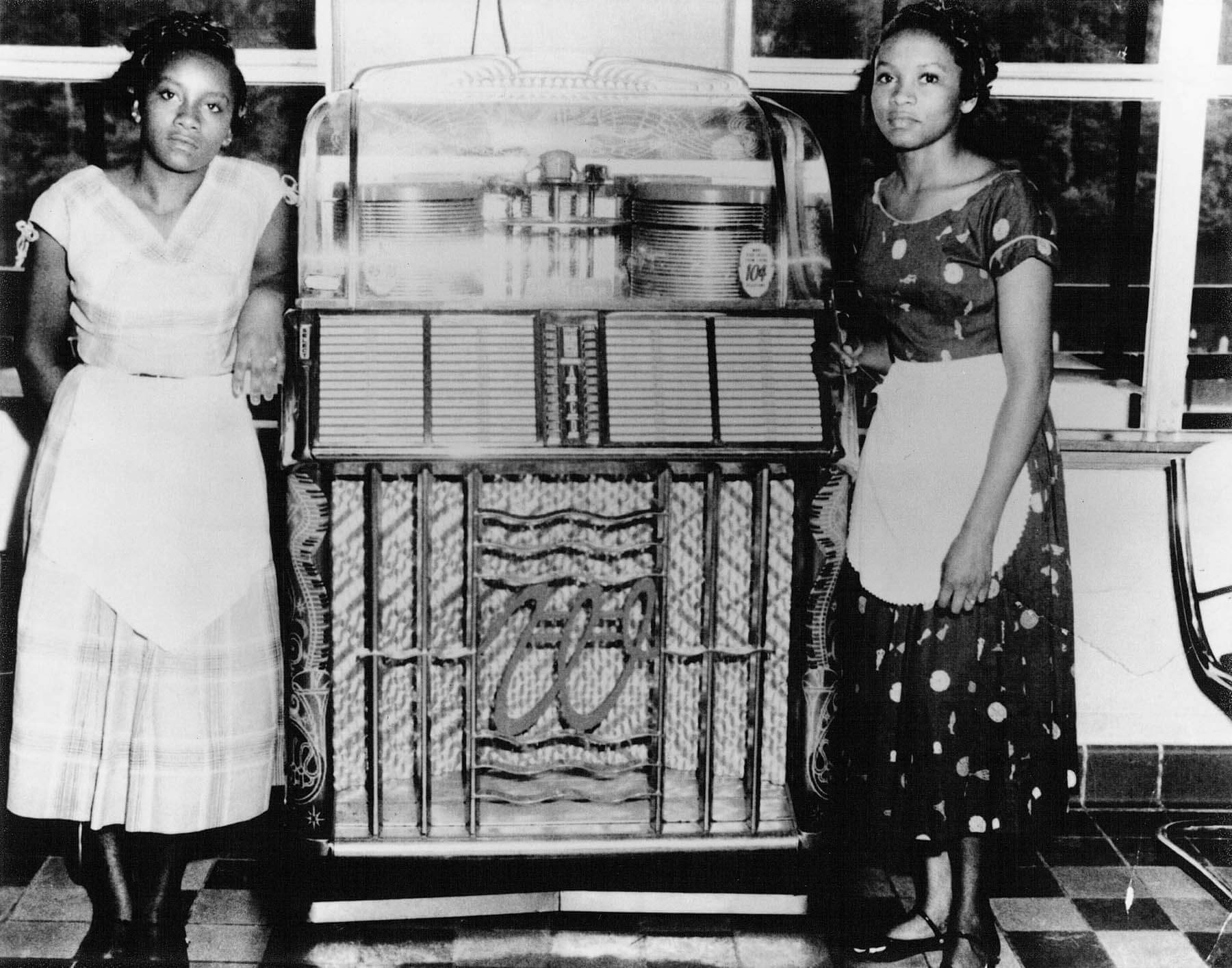Two woman pose by a jukebox in the dance hall.