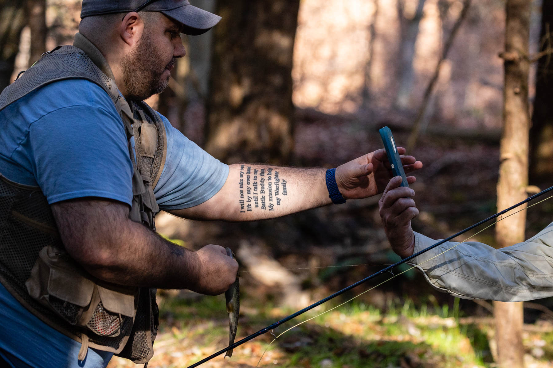 A male veteran looks at a photo a friend took of the fish he caught.