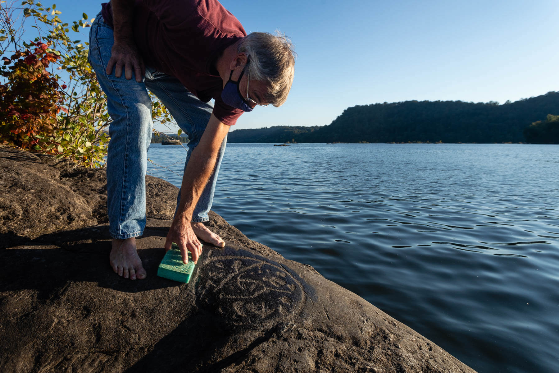 Petroglyph expert bends down to a carving in a river