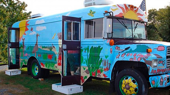 The fish mobile is a multi-colored school bus with an environmentally themed mural painted on it.