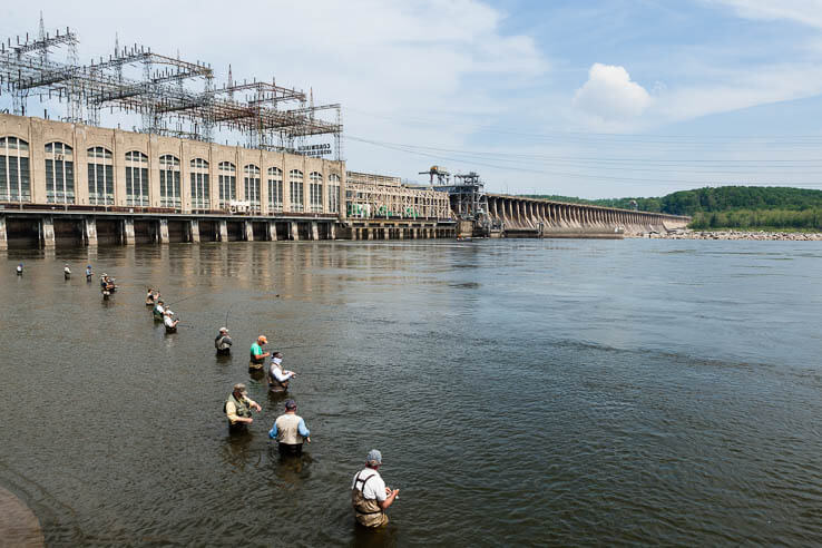 Line of anglers stand in river at foot of dam