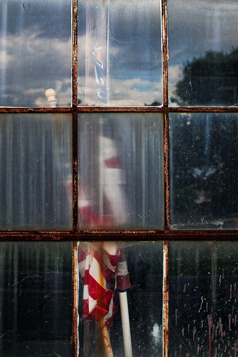 And American flag sits inside the window of a closed packing company.