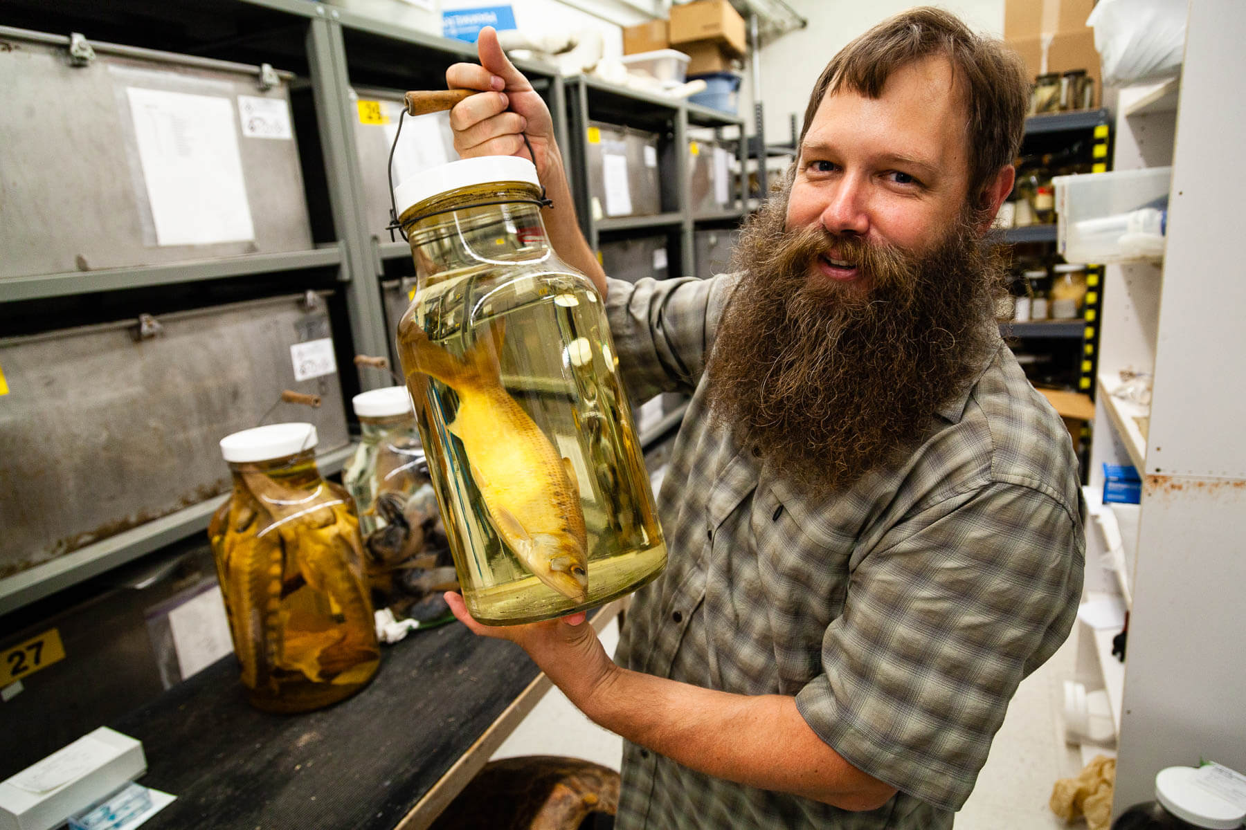 Bearded man holds a fish in a jar