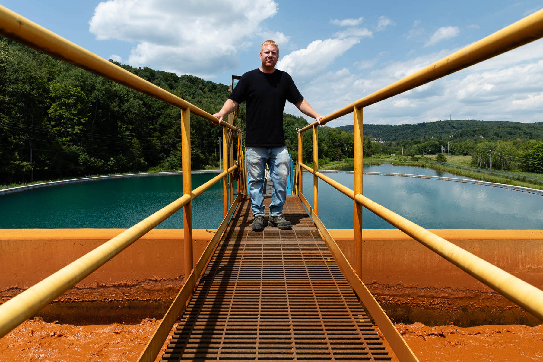 Mark Lloyd, engineer at the Lancashire Acid Mine Drainage Treatment Plant in Barr Township, Pa., poses on a catwalk above iron oxide sludge at the plant. The current plant, which opened in 2011, actively pumps water from the Lancashire No. 15 mine, treating roughly six million gallons of water daily to remove rust-colored iron oxide, before discharging the water into the West Branch. (Photo by Ethan Weston/Chesapeake Bay Program)