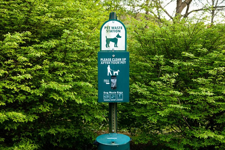 Pet waste station sign with plastic bags
