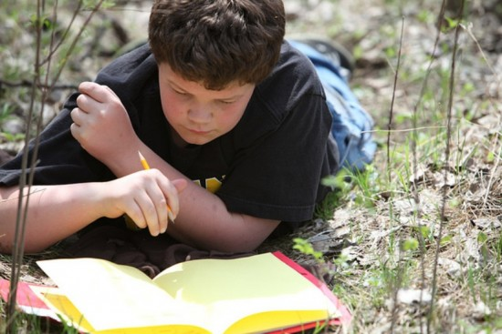 A boy writes in a nature journal outside in a forest.
