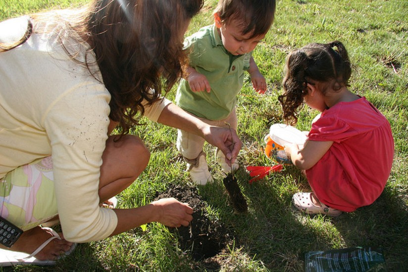 A woman plants seeds with two toddler girls on a sunny lawn.